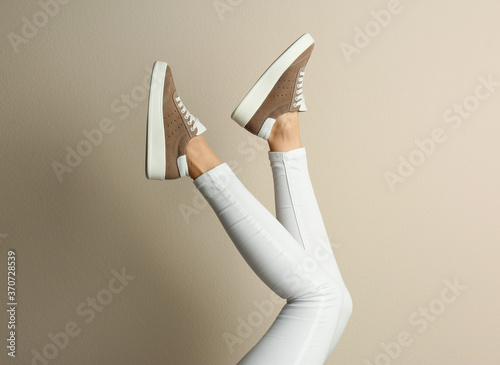Obraz Woman wearing shoes on beige background, closeup - fototapety do salonu