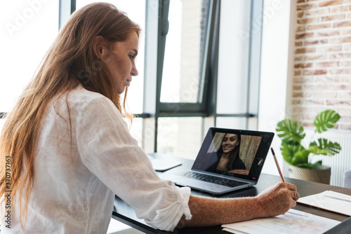 Fotografie, Obraz Image of businesswoman making call on laptop while sitting at table