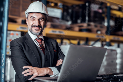 Obraz Businessman wearing a hardhat standing at goods warehouse and check for control loading from Cargo freight ship for import and export by report on laptop. commercial warehouse for trading concept - fototapety do salonu