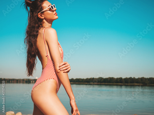 Obraz Young beautiful sexy hipster woman in sunglasses posing  on sea background.Trendy woman in summer swimwear bathing suit. Positive female going crazy.Funny model hugging herself - fototapety do salonu