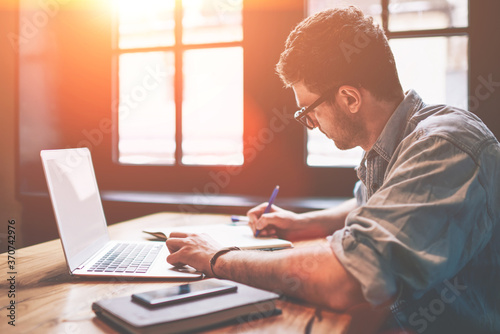 Fototapeta Young millennial male student searching information for homework using laptop and wifi connection indoors, man writing article in textbook for add interesting content on own website or web page obraz