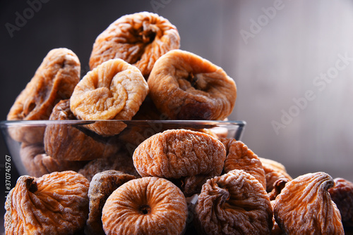 Fotografie, Obraz Composition with bowl of dried figs on wooden table
