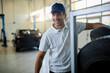Happy car mechanic working in auto repairs shop.
