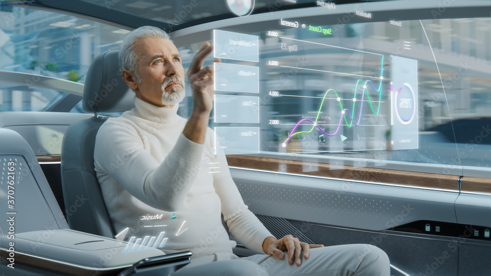 Fototapeta Attractive Senior Man Using Futuristic Augmented Reality Interface for Reading News and Checking Social Activity while Sitting on a Backseat of Autonomous Car. Self-Driving Van Rides on Public Road.