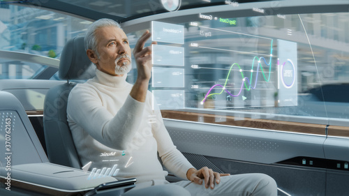 Obraz Attractive Senior Man Using Futuristic Augmented Reality Interface for Reading News and Checking Social Activity while Sitting on a Backseat of Autonomous Car. Self-Driving Van Rides on Public Road. - fototapety do salonu