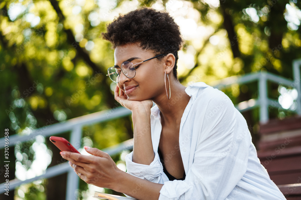 Fototapeta Woman sitting outdoors in park chatting by mobile phone