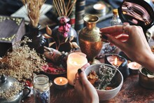 Female Wiccan Witch Holding Grey Clay Pot In Her Hands Preparing Ingredients For A Spell At Her Altar. Dried Plants, Herbs, Flowers, Lit Burning Candles, Gold Brass Vase And Old Bottles In Background