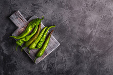 Hot Spicy Green Chili Peppers On Wooden Cutting Board, Stone Concrete Background, Top View Copy Space