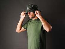 The Man Is Wearing A Green Camouflage Panama Hat And A Green T-shirt On A Grey Background.