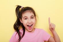 Niña De 5 A 8 Años Con Expresión Alegre Y Divertida Haciendo El Numero Uno Con El Dedo De La Mano Sobre Un Fondo Amarillo