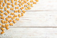Delicious Goldfish Crackers On White Wooden Table, Flat Lay. Space For Text
