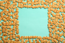 Frame Of Delicious Goldfish Crackers On Turquoise Background, Flat Lay. Space For Text