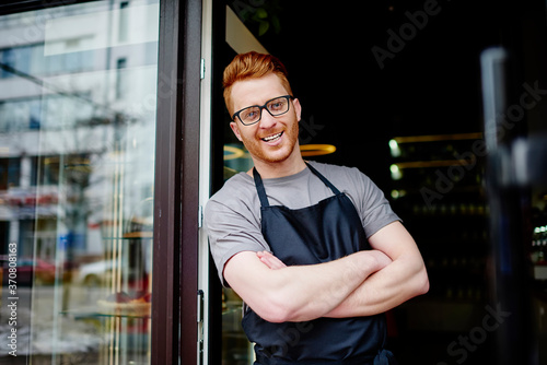 Fotografiet Portrait of successful and professional male barista with red hair and black apron smiling at camera