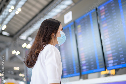 Obraz A traveller woman is wearing protective mask in International airport, travel under Covid-19 pandemic, safety travels, social distancing protocol, New normal travel concept - fototapety do salonu