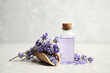 Bottle of essential oil and lavender flowers on light stone table