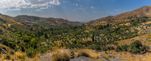 A Panorama View From The Sierra Nevada Mountains, Spain Toward The Village Of Monachil And The City Of Granada In The Distance In The Summertime