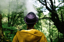 Back View Of Unrecognizable Female Traveler With Hooded Yellow Coat Exhaling Smoke And Looking Over Shoulder On Blurred Background Of Green Forest