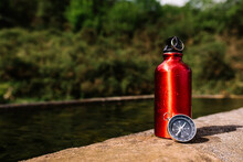 Metal Bottle With Fresh Water And Magnetic Compass Placed On Stone Border Near Pond In Park