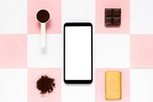 Top View Of Modern Cellphone With Empty Screen Surrounded By Measuring Spoon With Cocoa Powder And Square Cracker With Piece Of Dark Chocolate