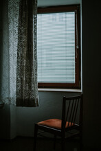 Chair Placed In Front Of A Windows Inside A Dark Room
