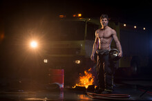 Muscular Fireman With Naked Torso Standing With Helmet Near Flame And Fire Truck While Looking At Camera