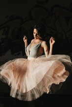 Beautiful Young Female Ballet Dancer In Translucent Tutu Performing Sensual Dance Movements In Dark Studio With Eyes Closed