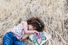 Adorable Calm Mulatto Girl In Trendy Dress Lying On Plaid On Wheat Field On Summer Day And Looking At Camera