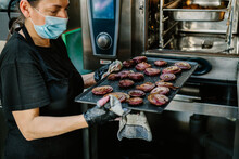 Crop Professional Female Chef In Face Mask And Gloves Taking Out Baking Pan With Roasted Red Onion Slices From Oven While Working In Restaurant Kitchen