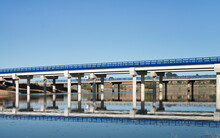 Amazing View Of Contemporary Metal Bridge Crossing River On Background Of Blue Cloudless Sky