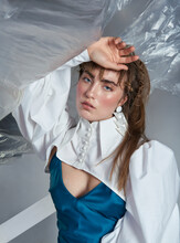 Stylish Young Woman In Formal Dress And Short Jacket With Lush Sleeves Standing Crumpled Plastic And Looking At Camera