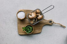 From Above Of Raw Mushrooms In Metal Container On Table Near Bowls With Salt And Parsley Placed On Wooden Cutting Board