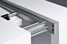 From Above Of Open Apparatus In Form Of Drawer With White Smooth Surface And Stainless Steel Parts Inside With Solid Structure Fixed With Bolts