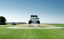Huge Agricultural Machine Driving Along Green Field And Watering Grass During Sunny Day