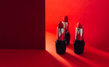 Set Of Bright Red Lipsticks In Elegant Shiny Tubes Placed On Red Background
