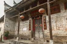 Exterior Of Aged Stone Building With Shabby Walls And Ornamental Doorway With Paper Lanterns In Yangshuo County