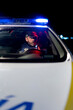 Male police officer sitting in parked automobile with siren light