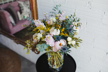 High Angle Of Beautiful Spring Bouquet With Assorted Colorful Blooming Flowers Including Pink Peonies And Blue Sea Holly Flowers With Mimosa Twigs Arranged On Glass Vase On Table Near White Wall