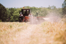 Tractor Driving And Harvesting Hay On Field