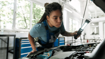 A little care for your vehicle. Young african american woman, professional female mechanic looking, examining under hood of car with torch at auto repair shop