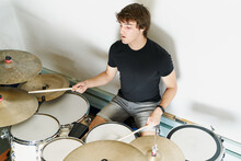 From Above Calm Focused Male Drummer Playing On Drum Kit Sitting On White Background Stage