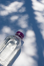 From Above Of Fresh Water In Transparent Plastic Bottle Placed On White Surface With Shadow