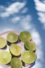 From Above Of Halves Of Ripe Limes Arranged On Pink Plate On Blue Background With Tree Shadows