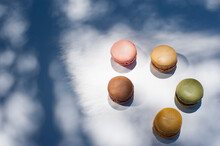 From Above Of Various Colorful Macarons Placed On White Background On Sunny Day
