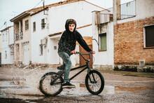 Teenage Boy Splashing Water In Puddle While Cycling On Street During Rainy Season