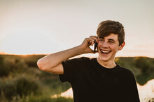 Happy Teenage Boy Talking Over Smart Phone While Standing Against Clear Sky During Sunset