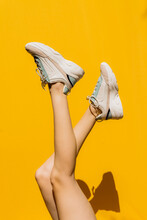 Woman's Legs In Sports Shoes Over Yellow Wall During Sunny Day