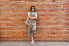 Young Woman Wearing Mask With Arms Crossed Leaning On Brick Wall