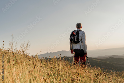 Retired senior man standing by cattail plants while looking at landscape during sunset