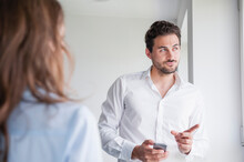 Confident Businessman Pointing While Discussing With Female Colleague In Office