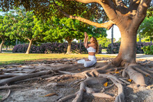 Mature Woman Mediating While Sitting On Roots In Park
